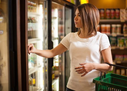 Commercial Refrigeration- Glacier Refrigeration Heating and Air-conditioning: Woman opening door of supermarket fridge in Melbourne